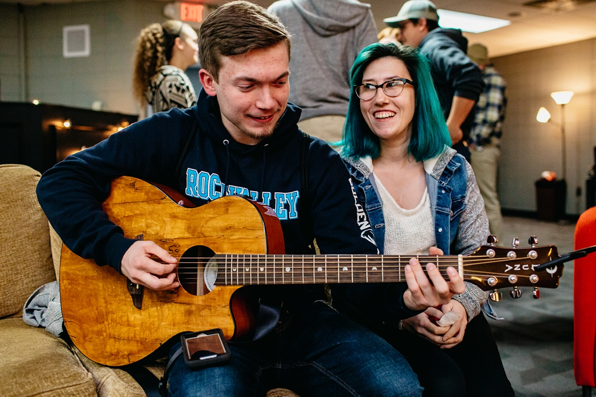 Young Adults hanging out playing guitar